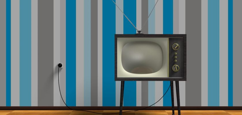 An old tv kept in front a blue wall