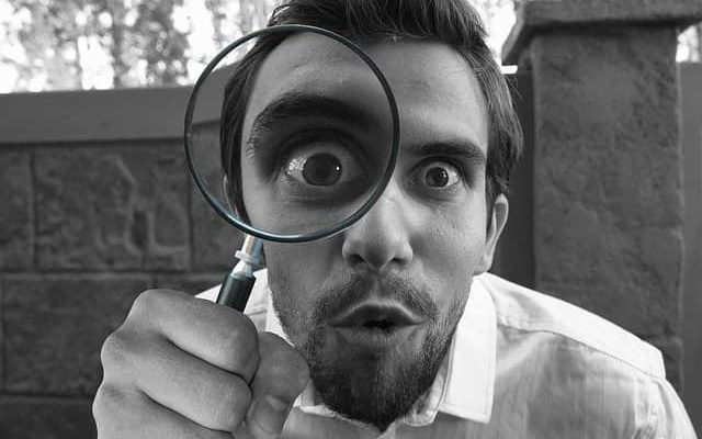 Man staring through a magnifying glass